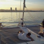 Gente viendo puesta de sol y descansando en cubierta de Catamarán